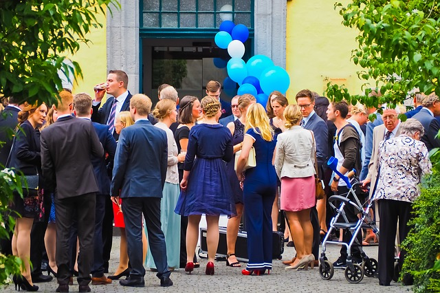 svatebčané se sešli před budovou, hodně jich stojí zády, muži v oblecích, ženy v šatech nebo sukních, modré balónky v pozadí