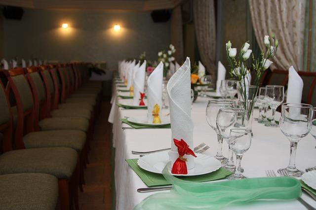prostřený stůl na svatbu, ubrousky na stojku, zelené ubrousky, sklenice, mnoho židlí