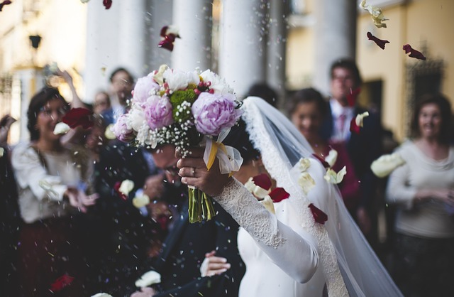 a photo of a bride holding her buquet high above her head